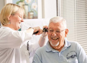 Senior man smiling as a nurse checks his ear
